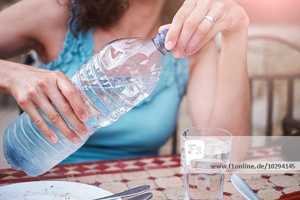 Abgeschnittene Aufnahme einer reifen Frau  die ein Glas abgefülltes Wasser auf den Tisch gießt. Abgeschnittene Aufnahme einer reifen Frau, die ein Glas abgefülltes Wasser auf den Tisch gießt.
