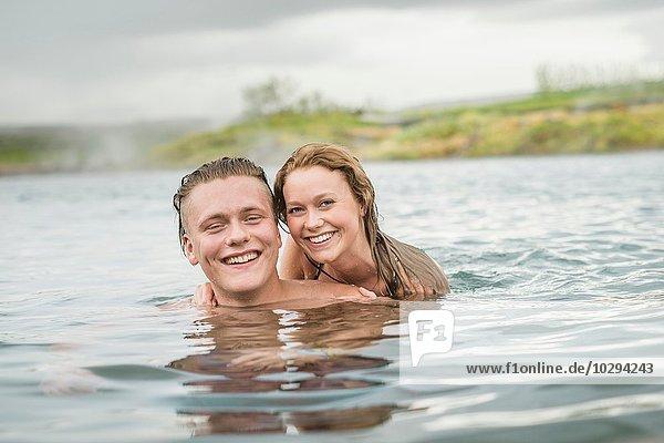 Porträt eines lächelnden jungen Paares  das sich in der Secret Lagoon Thermalquelle (Gamla Laugin)  Fludir  Island  entspannt.