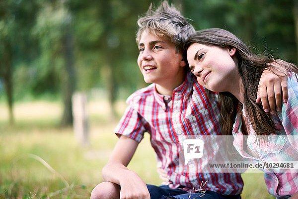 Portrait of teenage boy with arm around sister