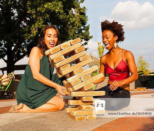 Junge Frauen spielen mit Bausteinen auf dem Boden