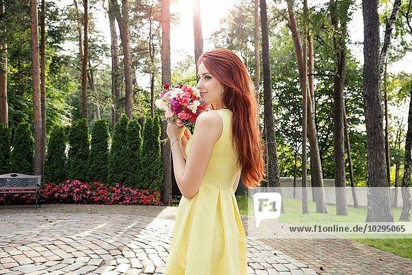 Junge Frau mit Blumenstrauß im Park