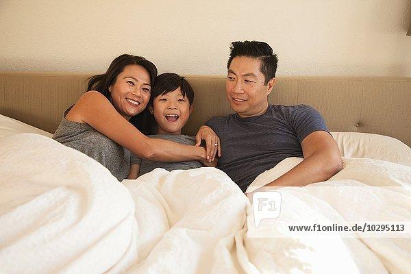Porträt von reifen Eltern und Sohn im Bett
