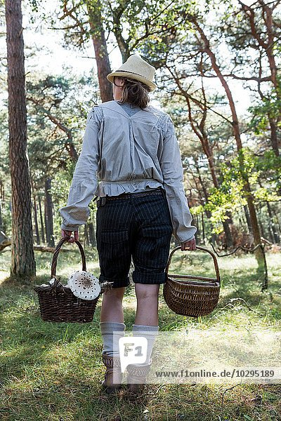 Rear view of female forager carrying baskets of mushrooms in forest