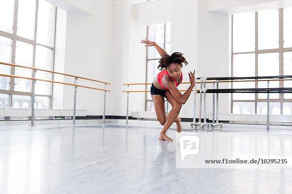 Junge Frau im Tanzstudio tanzt mit Blick auf die Kamera