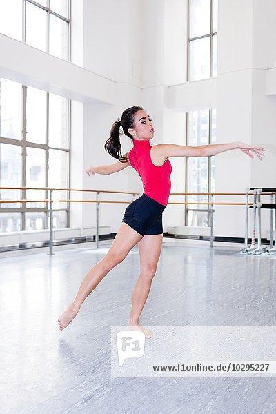 Junge Frau im Tanzstudio tanzende Arme öffnen sich und schauen weg