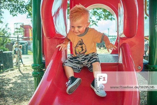 Ein kleiner Junge spielt auf einer roten Spielplatzrutsche.
