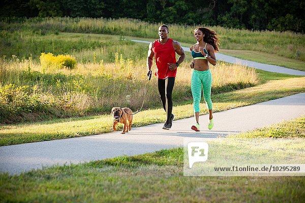 Junges Paar und Hund beim Laufen im Park