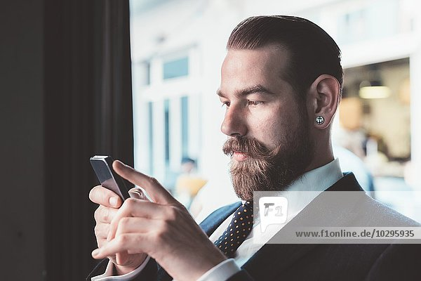 Businessman reading smartphone update in cafe