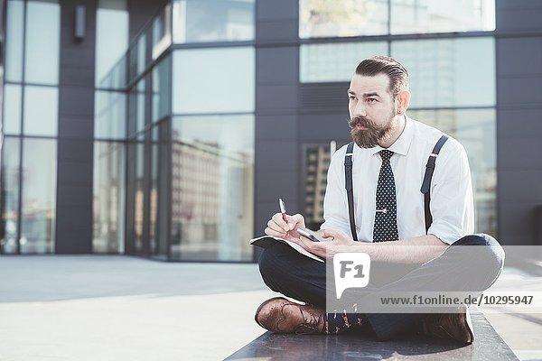 Stilvoller Geschäftsmann sitzt im Kreuzbein und macht Tagebuchnotizen vom Smartphone außerhalb des Büros.