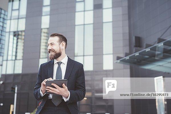 Stilvoller bärtiger Geschäftsmann mit digitalem Tablett-Touchscreen außerhalb des Büros