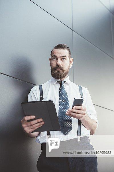 Stilvoller Geschäftsmann mit Smartphone und digitalem Tablett  das sich an die Bürowand lehnt