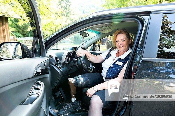 Porträt einer mittleren erwachsenen Frau mit Beinprothese  im Auto sitzend