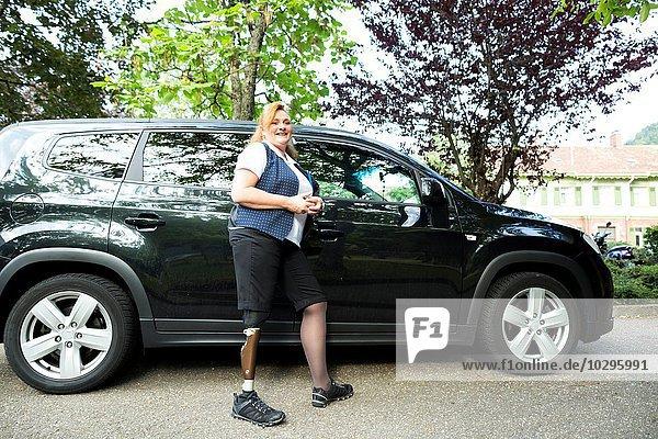 Porträt einer mittleren erwachsenen Frau mit Beinprothese  neben dem Auto stehend