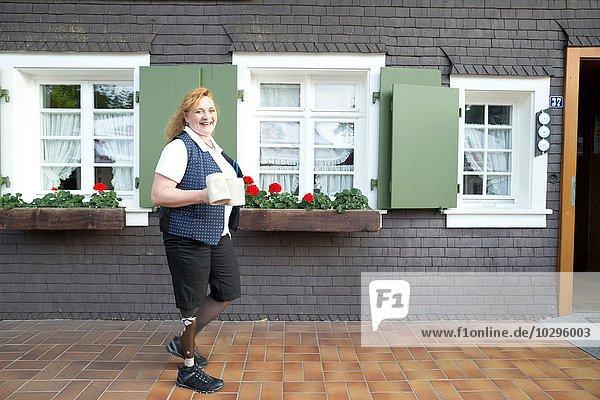 Mittlere erwachsene Frau mit Beinprothese  Tragebecher  im Freien