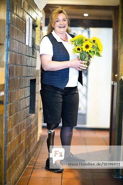 Porträt einer mittleren erwachsenen Frau mit Beinprothese  stehend  Blumen haltend