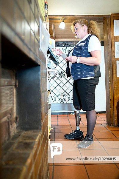 Mittlere erwachsene Frau mit Beinprothese  arbeitende Kasse im Restaurant