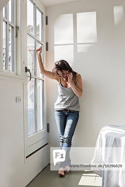 Reife Frau steht im teilmöblierten Haus  spricht auf dem Handy