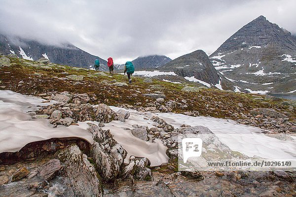 Rear view of three hikers hiking across frozen landscape  Ural mountains  Russia