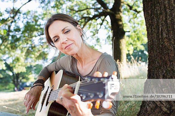 Reife Frau spielt Akustikgitarre im Park