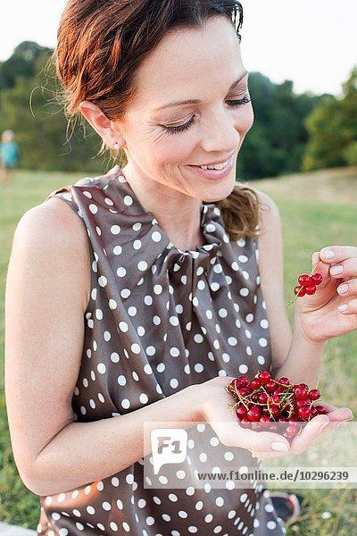 Reife Frau beim Essen von roten Johannisbeeren im Park