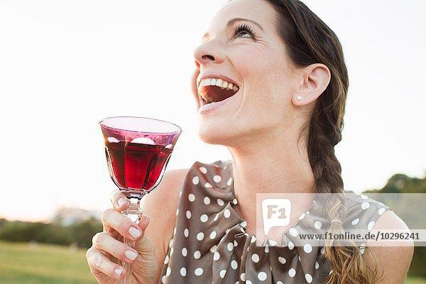Reife Frau lacht  während sie im Park ein Glas Rotwein trinkt.