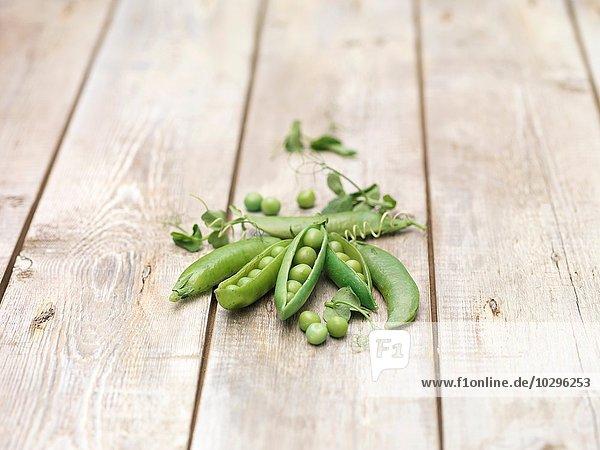 Stilleben von grünen Erbsen in Schoten mit Erbsensprossen auf Holztisch