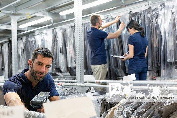 Drei Lagerarbeiter bei der Vorbereitung der Kleidungsstücke im Distributionslager
