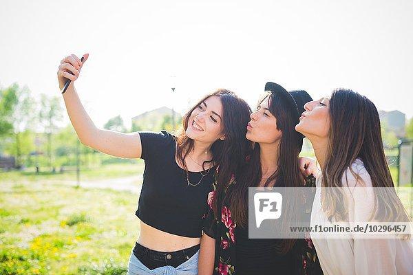 Drei junge Freundinnen kräuseln Lippen für Smartphone Selfie im Park