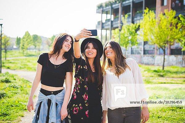 Drei junge Freundinnen posieren für Smartphone Selfie im Park