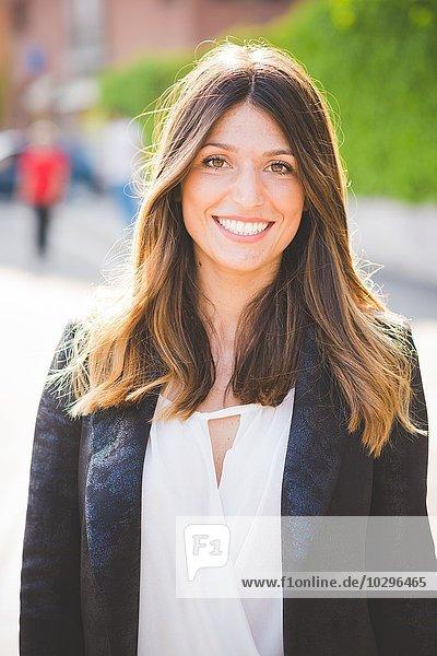 Porträt einer glücklichen jungen Frau mit langen braunen Haaren