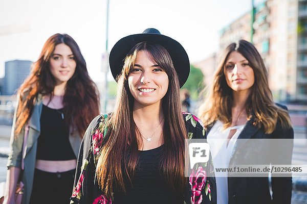 Portrait of three young women in city
