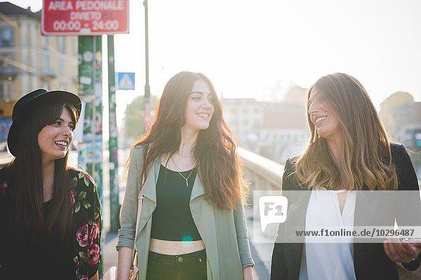 Drei junge Frauen beim Bummeln und Plaudern in der Stadt