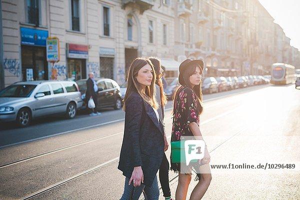 Drei junge Frauen  die auf der Stadtstraße spazieren gehen.