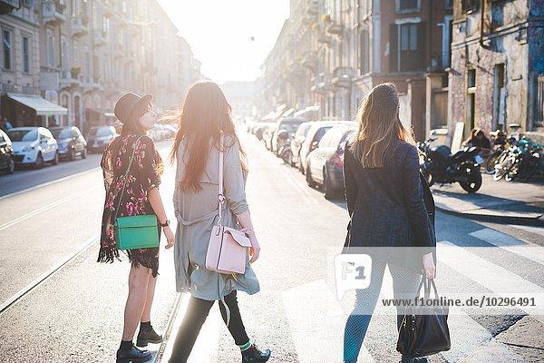 Rückansicht von drei jungen Frauen  die über den Fußgängerüberweg schlendern