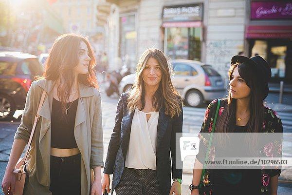 Drei junge Frauen,  die auf der Straße spazieren gehen.
