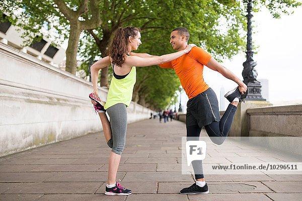 Männliche und weibliche Stadtläufer beim Aufwärmen