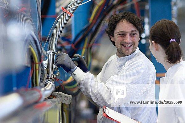 Männliche und weibliche Kollegen im Laborkittel  von Angesicht zu Angesicht lächelnd