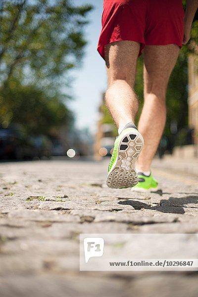 Läufer joggen auf gepflasterter Straße