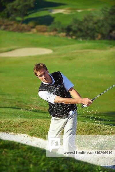 Golfer beim Golfschwung in der Sandfalle  Golfball in der Luft