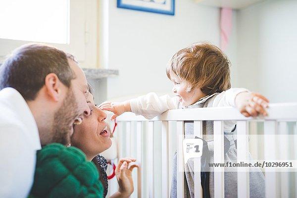 Mittleres erwachsenes Paar lacht mit Kleinkind-Tochter in Krippe
