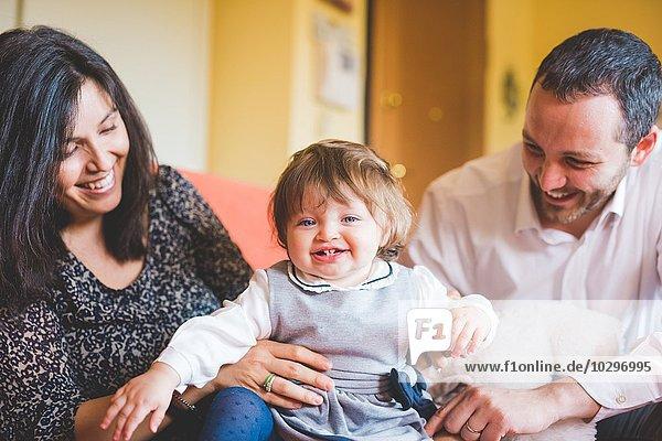Mittleres erwachsenes Paar spielt mit Kleinkind-Tochter auf Sofa
