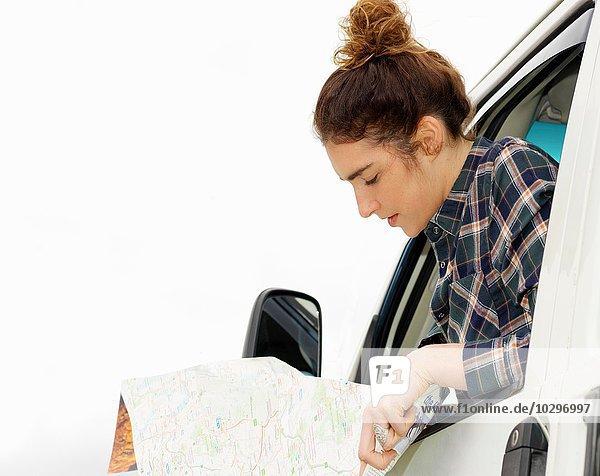 Junge Frau liest Karte aus dem Wohnmobilfenster