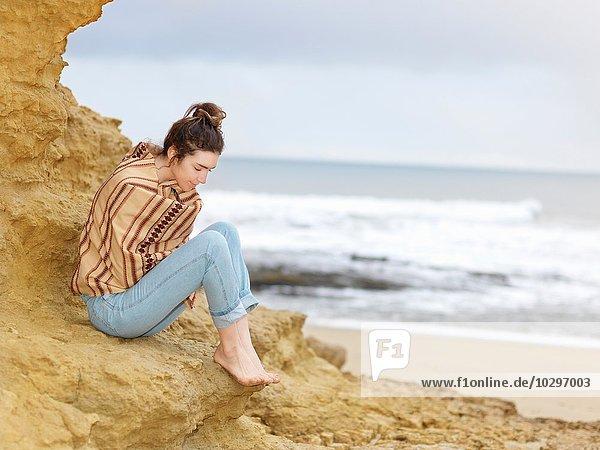 Junge Frau in Schal gewickelt auf Klippe sitzend  Point Addis  Anglesea  Victoria  Australien