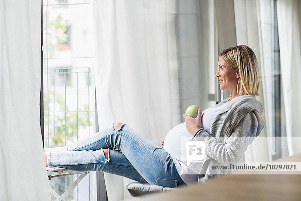 Vollzeitschwangerschaft junge Frau beim Apfelessen