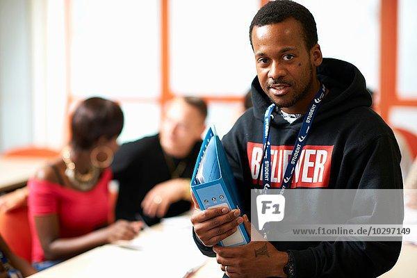 Porträt eines männlichen Schülers  der die Akte vor der Klasse hält.