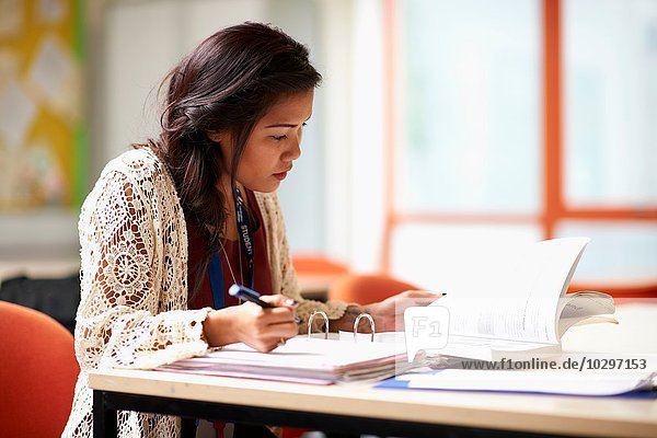 Junge Studentin beim Schreiben in der Akte