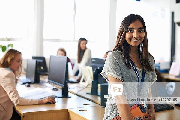 Porträt einer lächelnden Schülerin  die eine Akte in der Klasse hält.
