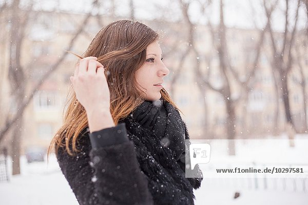 Young woman playing with her hair  wintry background