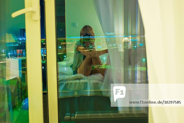 Junge Frau auf dem Bett im Zimmer sitzend