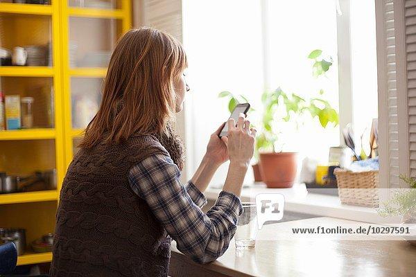 Junge Frau mit Smartphone am Tisch